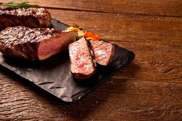 Bife grelhado em fatias em uma placa de corte preta sobre a mesa de madeira.