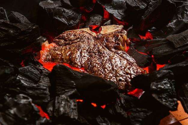 Bife grelhado em mármore com brasas e fumaça