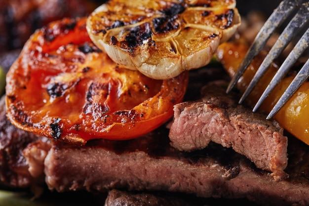 Bife grelhado em uma panela preta e um pedaço de picado em um garfo com legumes cozidos