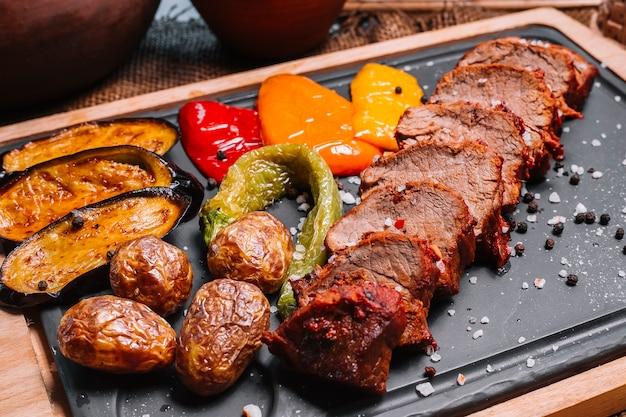 Bife grelhado fatiado na tábua de madeira berinjela batata pimentão vista lateral
