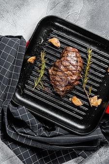 Bife grelhado flat iron em uma panela de grelhar, carne marmorizada. vista do topo