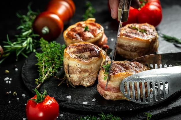Bife grelhado pelo chef com as mãos em fundo preto. filé mignon bife filé mignon com bacon coberto com especiarias. vista do topo.