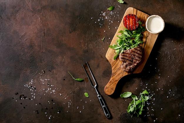 Bife grelhado servido com molho cremoso, tomate de legumes grelhados e salada de rúcula na tábua de madeira sobre fundo de textura marrom escuro. vista superior, configuração plana. copie o espaço