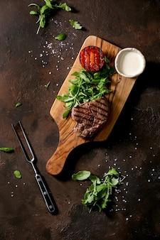 Bife grelhado servido com molho cremoso, tomate de vegetais grelhados e salada de rúcula na tábua de madeira com garfo de carne sobre a superfície de textura marrom escura. vista superior, configuração plana