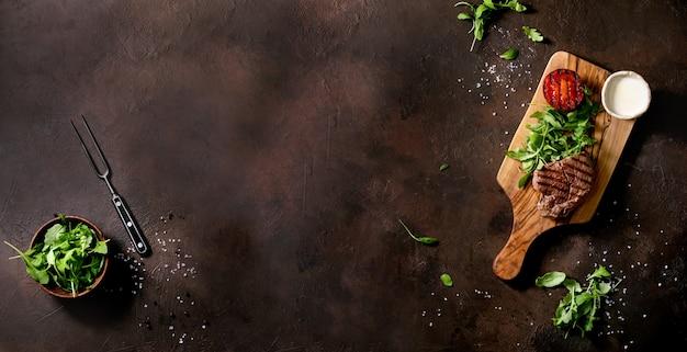 Bife grelhado servido com molho cremoso, tomate de vegetais grelhados e salada de rúcula na tábua de madeira sobre a superfície de textura marrom. vista superior, configuração plana. copie o espaço. tamanho do banner