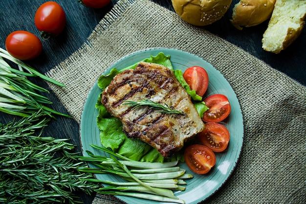 Bife grelhado servido em um prato, decorado com temperos para carne, alecrim, verduras e legumes.