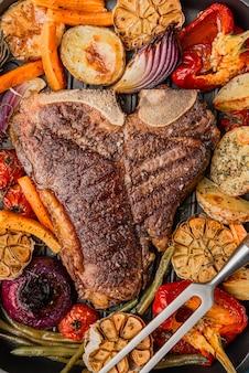 Bife macio e suculento no osso grelhado ao lado de legumes cozidos e grelhados, o conceito de nutrição saborosa e saudável