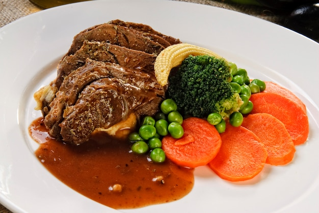 Bife marinado e grelhado, rodeado por legumes frescos.