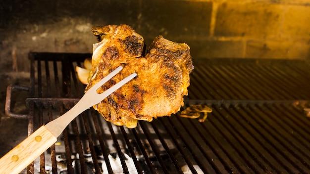 Bife marrom dourado grelhado no garfo
