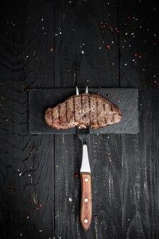 Bife no garfo no fundo escuro de madeira. banner, lugar de receita de menu para texto, imagem vertical de vista superior.