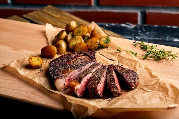 Bife ribeye muito suculento de carne marmorizada em uma mesa de madeira com batatas bebê