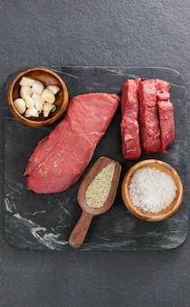 Bife, sal e especiarias na placa de ardósia preta