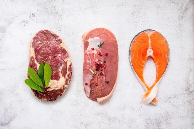 Bife, salmão e bife de olho de lombo em fundo de mármore branco