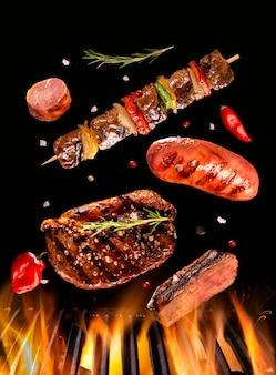 Bife, salsicha e carne no espeto caindo na grelha com fogo. churrasco brasileiro.