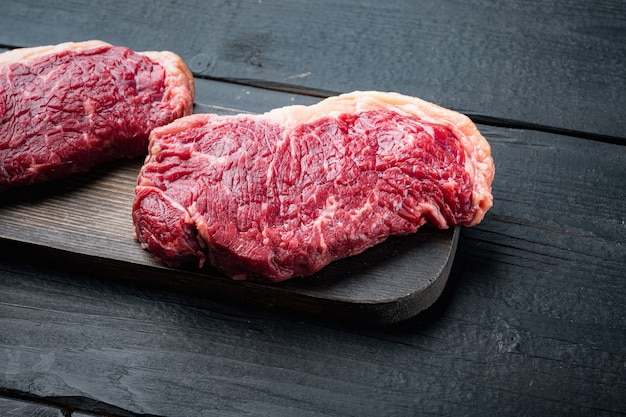 Bife striploin, corte de açougue de carne crua, em mesa de madeira preta