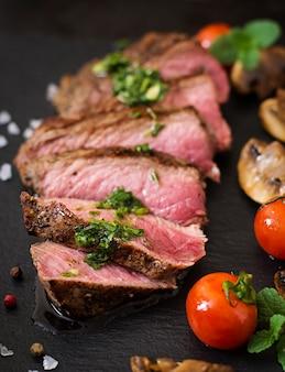 Bife suculento médio raro com especiarias e legumes grelhados.