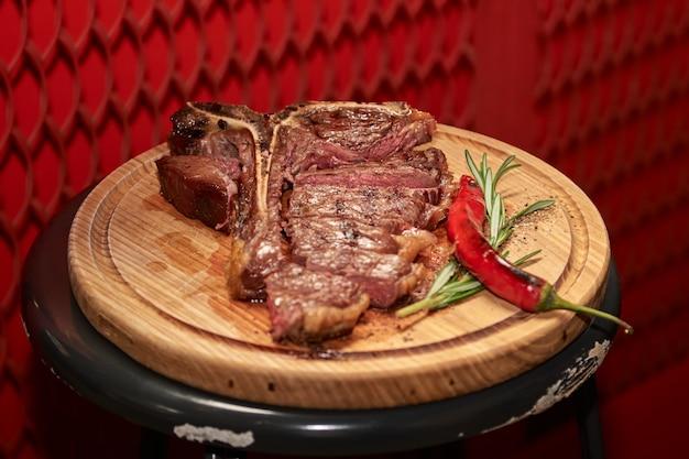 Bife t bone carne grelhada com ramo de alecrim pimenta sal e copo de cerveja em restaurante