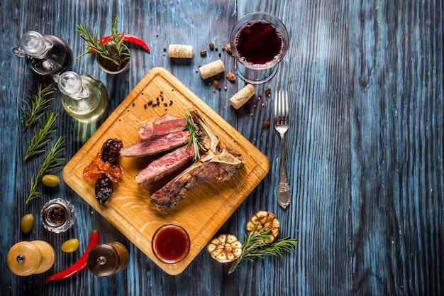 Bife t-bone grelhado raro médio fatiado em fundo de madeira rústico com alecrim e especiarias