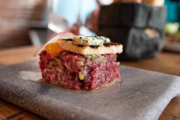 Bife tártaro com gema cremosa e brioche tostado com manteiga e vinho de sálvia