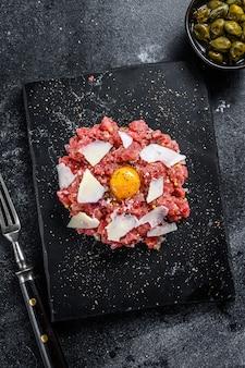 Bife tártaro com ovo de codorna, alcaparras e queijo parmesão. fundo preto. vista do topo.