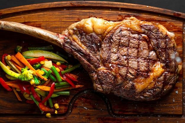 Bife tomahawk e vegetais em uma tábua de servir. imagem low key, orientação horizontal