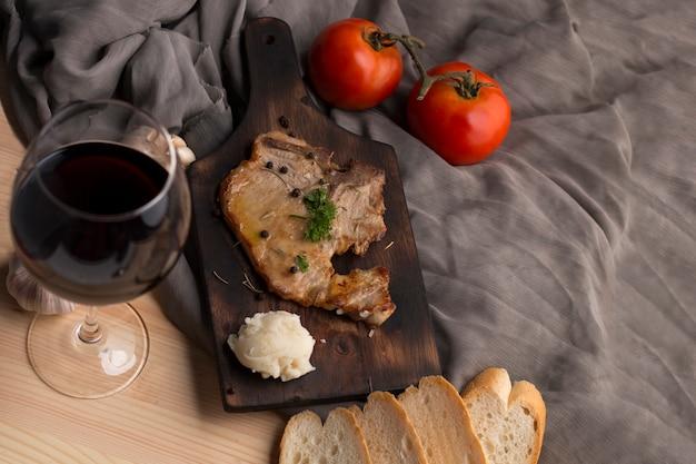 Bife, tomate, salsa, alho, pimenta preta e vinho em madeira e tecido.