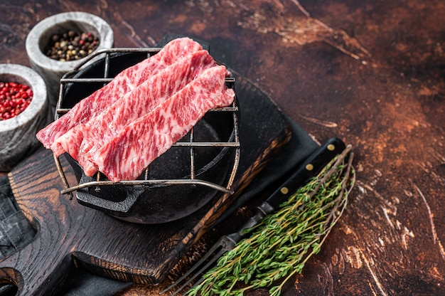 Bifes a5 de carne wagyu fatiada crua premium em uma grelha para yakiniku. alimentos japoneses. fundo escuro. vista do topo. copie o espaço.