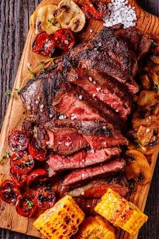 Bifes com tomate grelhado, cogumelos e milho.