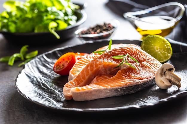 Bifes crus de salmão, tomates, alecrim, cogumelo, limão, azeite e especiarias - close-up.