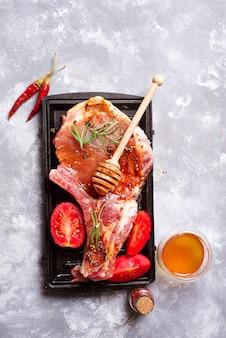 Bifes crus e frigideiras com temperos, guarnições e ingredientes em uma parte traseira rústica escura