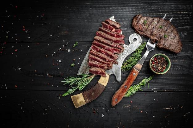 Bifes de alcatra de carne sobre a faca de açougueiro de carne com fundo escuro de especiarias. vista do topo.