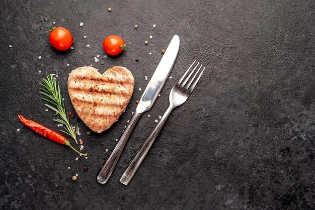Bifes de atum grelhados em forma de coração sobre fundo de pedra