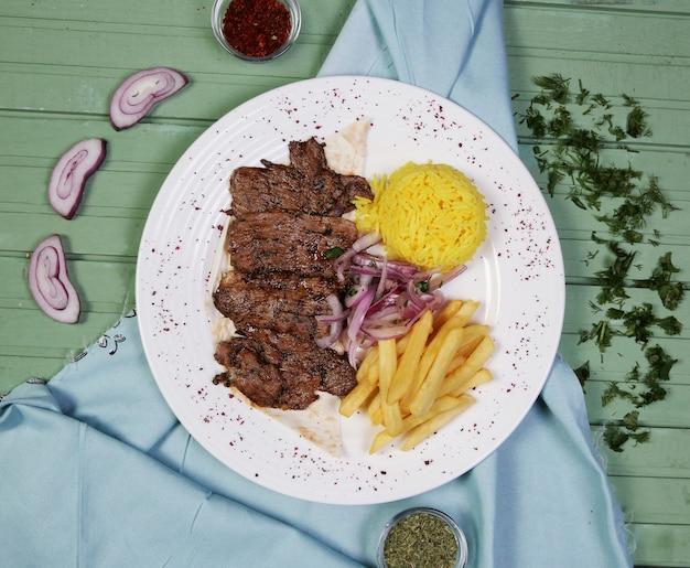 Bifes de carne com batatas fritas e guarnição de arroz dentro de chapa branca