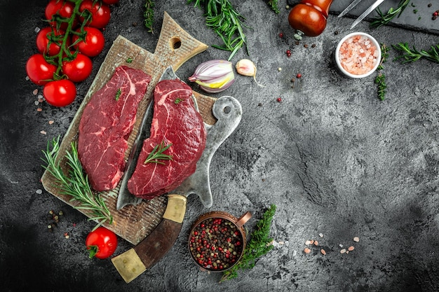 Bifes de carne crua com alecrim. seque o bife envelhecido com ervas e sal. restaurante americano de carnes. banner, lugar de receita de menu para texto, vista superior.