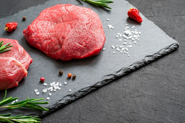Bifes de carne crua e alecrim em uma placa de ardósia preta.