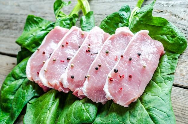 Bifes de carne crua em folhas de espinafre