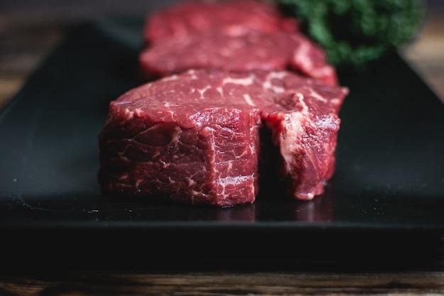 Bifes de carne crua em um prato preto