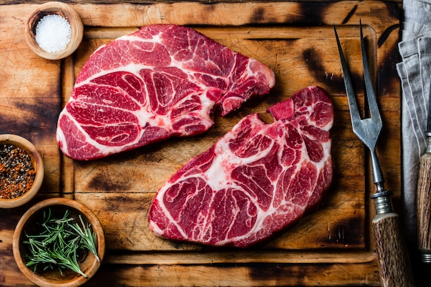Bifes de carne crua marmorizada na tábua de madeira