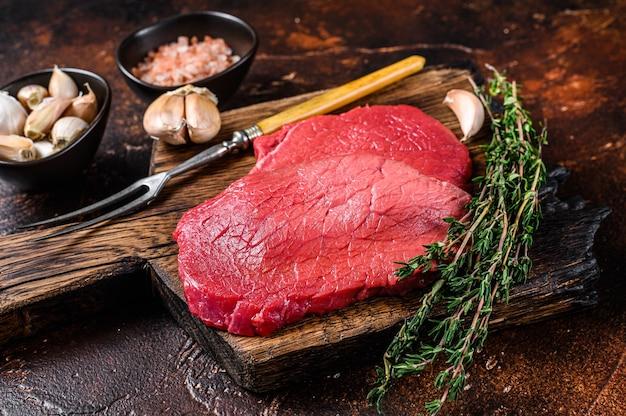 Bifes de carne de alcatra crua em tábua de açougueiro
