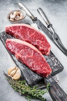 Bifes de carne de alcatra crua na placa de madeira com garfo e faca de carne. fundo branco. vista do topo.
