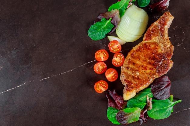 Bifes de carne de porco com legumes grelhados e tempero em fundo escuro