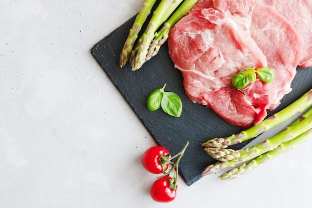 Bifes de carne de porco crua fresca mentem sobre uma tábua de pedra preta, ao lado de espargos verdes