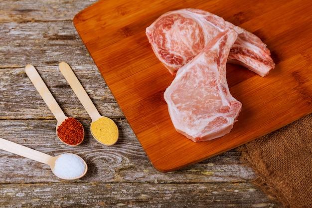 Bifes de carne de porco crua na placa de madeira com ervas, alho, especiarias e tomates prontos para cozinhar.
