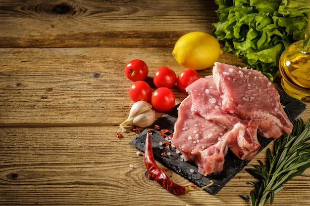 Bifes de carne de porco crua na placa de pedra com ervas, tomate, alho e limão.