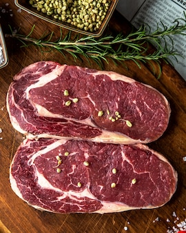 Bifes de carne na placa de madeira especiarias vista superior