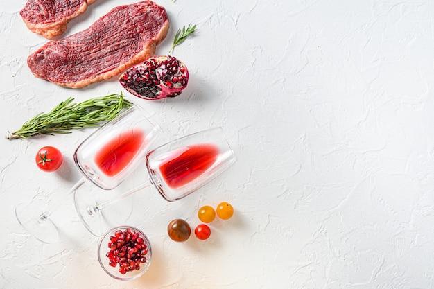 Bifes de carne orgânica picanha com alecrim, pimenta, romã, perto de vinho tinto em copos e garrafa sobre fundo branco texturizado, vista superior com espaço para texto.