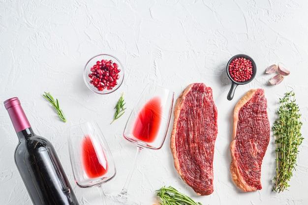 Bifes de carne orgânica picanha com temperos, perto de vinho tinto em copos e garrafa sobre fundo branco texturizado, vista superior com espaço para texto.