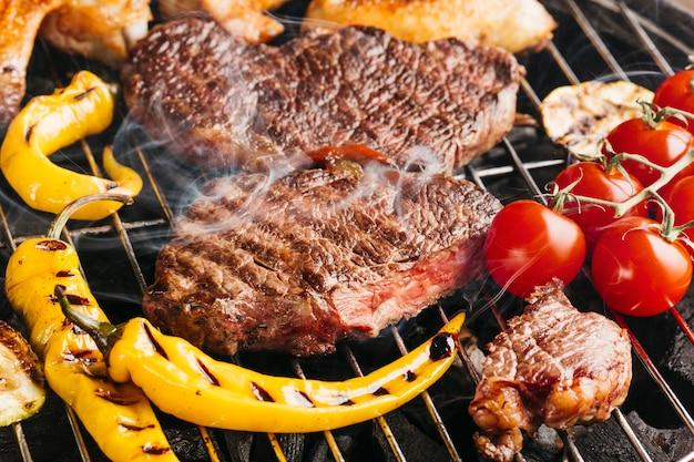 Bifes de carne saboroso na grelha com pimentão amarelo e tomate cereja