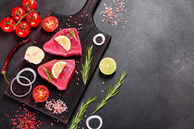 Bifes de filé de atum fresco com especiarias e ervas em um fundo preto