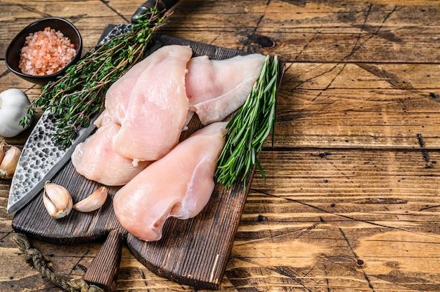 Bifes de filé de peito de frango cortado em fatias frescas cruas em uma tábua de madeira com uma faca de cozinha. fundo de madeira. vista do topo. copie o espaço.